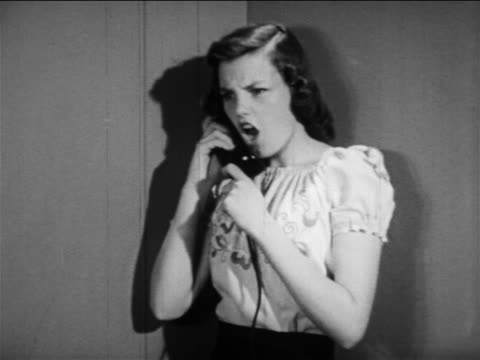 b/w 1949 girl standing in corner talking angrily on telephone + slams phone on cradle / educational - anger stock videos & royalty-free footage