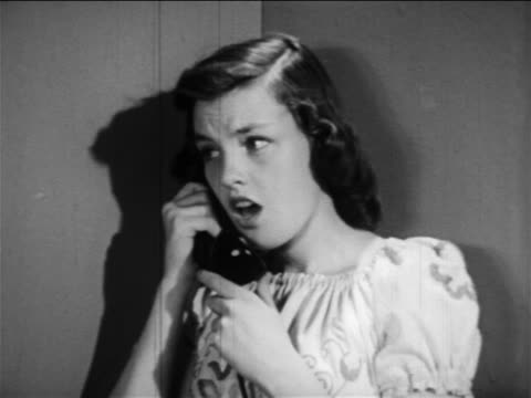 vídeos de stock, filmes e b-roll de b/w 1949 girl standing in corner talking on telephone / educational - only teenage girls