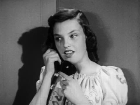 vídeos de stock, filmes e b-roll de b/w 1949 girl standing in corner talking on telephone / hangs up phone + talking to herself / edu. - only teenage girls