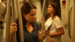 girl standing in underground carriage and using mobile phone