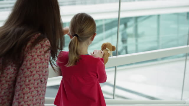 MS R/F Girl (6-7) standing next to mummy at airport on glass walkway waving to daddy in distance / Toulouse, Haute-Garonne, France