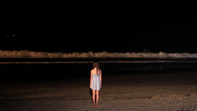 ms girl standing on beach and watching wave crash on shore at night, great ocean road / torquay, victoria, australia - 打ち寄せる波点の映像素材/bロール