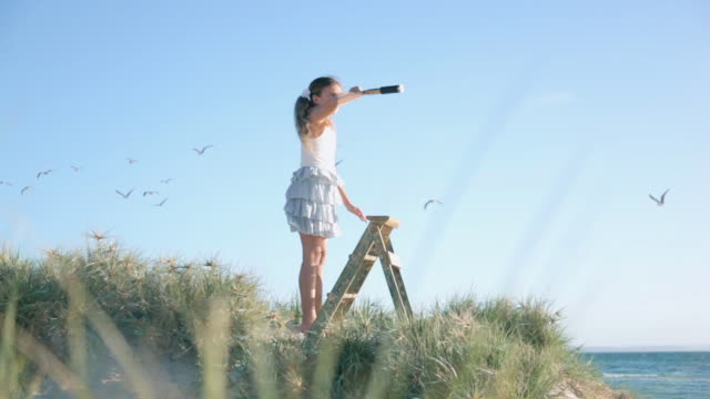ws girl standing on ladder looking through telescope at beach / melbourne, victoria, australia - looking through an object stock videos and b-roll footage
