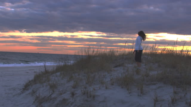 SLO MO WS Girl standing on sand dunes and tossing her hair back at sunset