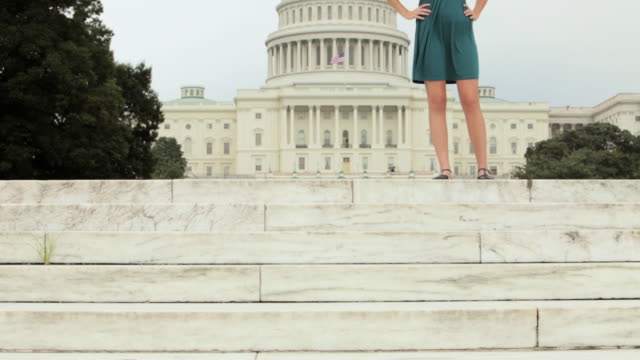 stockvideo's en b-roll-footage met girl standing on steps in front of united states capitol - handen op de heupen
