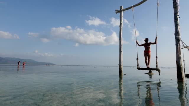 girl standing on swing at the beach in gili trawangan island in bali - bali stock videos & royalty-free footage