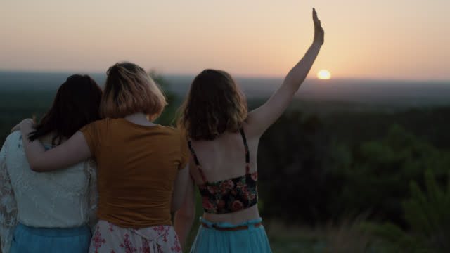 ws slo mo. girl standing with friends on mountainside waves hand in air and looks out over green valley at sunset. - winken stock-videos und b-roll-filmmaterial