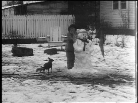 B/W 1944 girl stands behind snowman with American flag / dog + puppies wander away / home movie