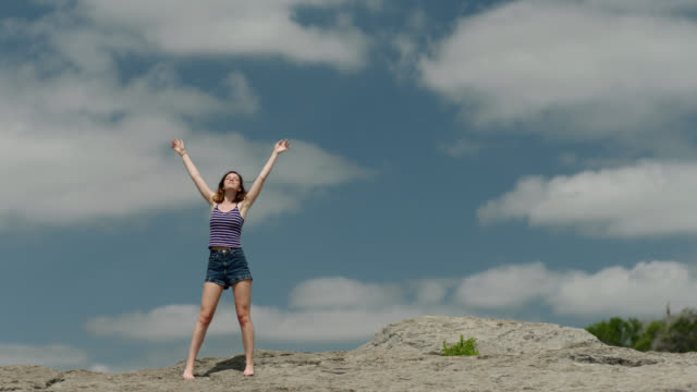ws slo mo. girl stands on rocky mountaintop and holds hands up in cloudy blue sky. - kopf nach hinten stock-videos und b-roll-filmmaterial