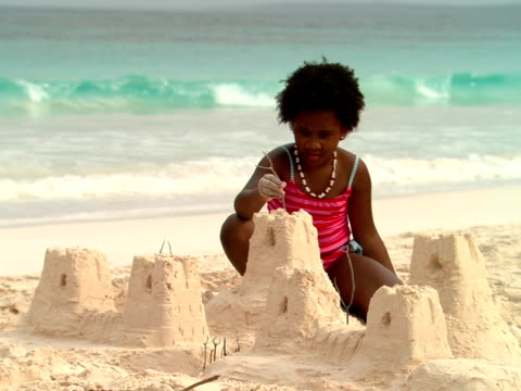 ms,  girl (8-9 years) sticking twig on top of sand castle,  harbour island,   bahamas - 8 9 years stock videos & royalty-free footage