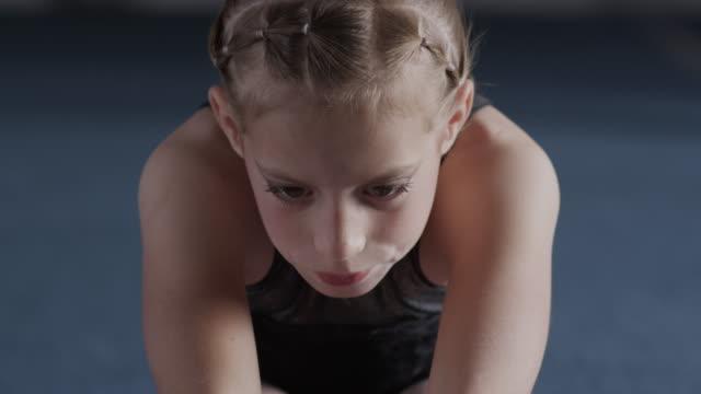 CU TU TD Girl (8-9) stretching in gym, Orem, Utah, USA