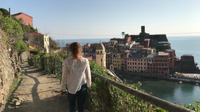 A girl strolling along the Sentiero Azzurro (the blue path) overlooking Vernazza. Cinque Terre