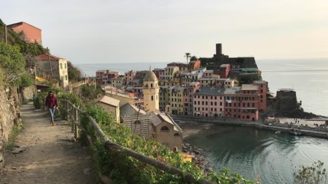 A girl strolling along the Sentiero Azzurro (the blue path) overlooking Vernazza. Cinque Terre