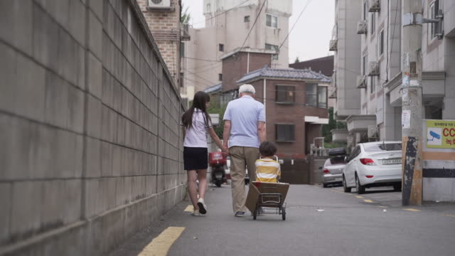 girl student and boy heading home with their grandfather, seoul, south korea - ソウル点の映像素材/bロール