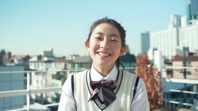 a girl student in uniform is smiling on the roof - schoolgirl stock videos & royalty-free footage