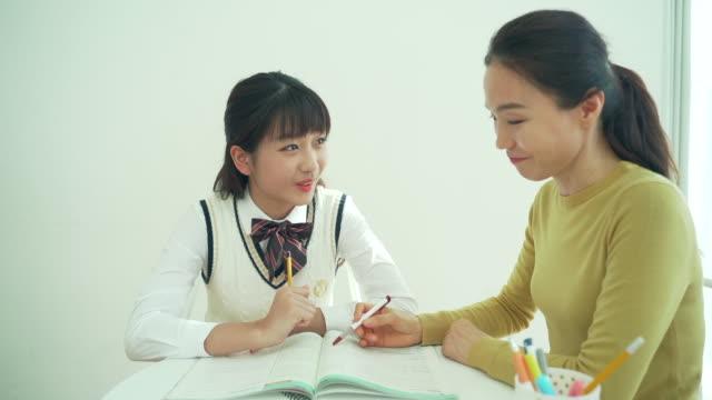 vídeos y material grabado en eventos de stock de a girl student in uniform studies with her mother in the room - coreano oriental