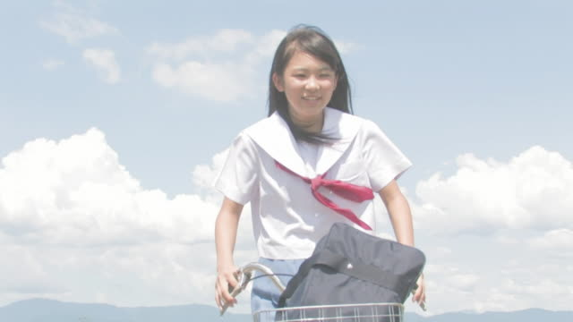 girl student riding bicycle - japanese school uniform stock videos & royalty-free footage