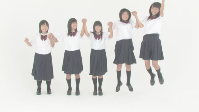Girl students jumping up hand in hand