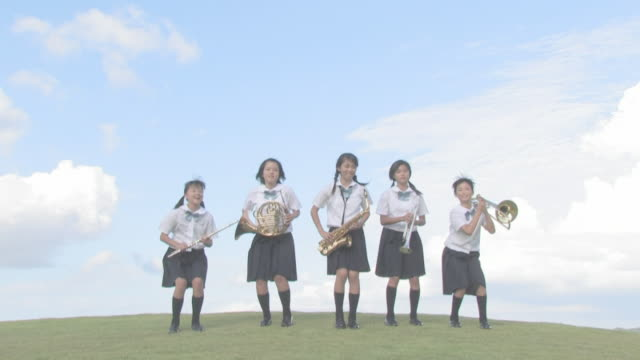 stockvideo's en b-roll-footage met girl students playing music on hill - middelbare scholiere