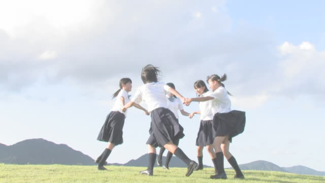 stockvideo's en b-roll-footage met girl students playing on hill - middelbare scholiere