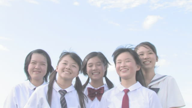 Girl students smiling with sky in background