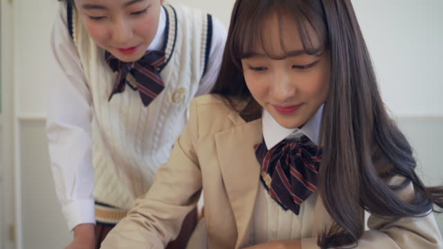 girl students study together with tablet pc in the classroom - ノート点の映像素材/bロール