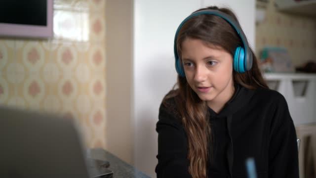 自宅でラップトップを介してビデオ通話を勉強し、ビデオ通話をする女の子 - remote location点の映像素材/bロール