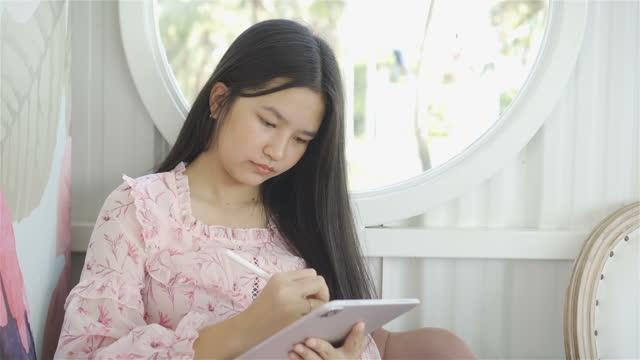 mädchen studieren und machen einen videoanruf über tablet zu hause - tablet benutzen stock-videos und b-roll-filmmaterial