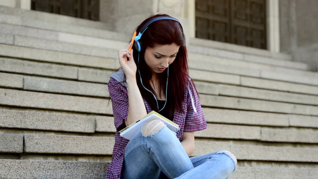 girl studying on stairs in campus - audio equipment stock videos & royalty-free footage