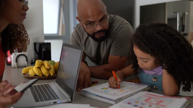 girl studying with father's support and mother working at home - two parents stock videos & royalty-free footage