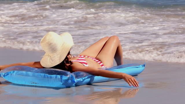 vídeos y material grabado en eventos de stock de girl sunbathing on a lilo on the beach getting splashed by the waves - sólo una adolescente