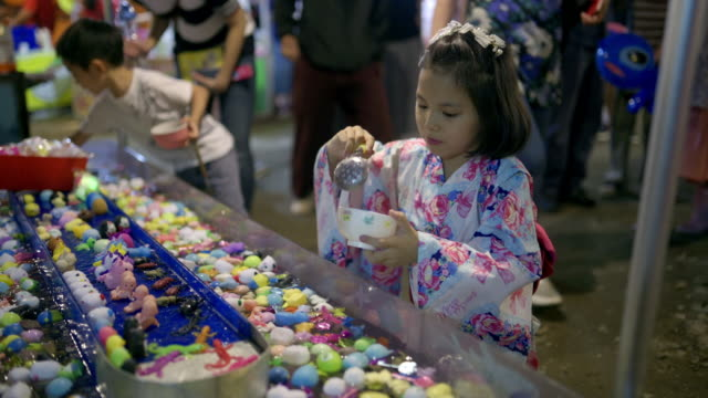 girl superball scooping, festival game in which one scoops up rubber bouncy balls floating in water - 伝統的な祭り点の映像素材/bロール