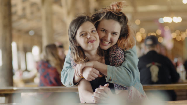 ms slo mo. girl surprises her sister with a hug and they smile at camera together in family restaurant. - sorpresa video stock e b–roll