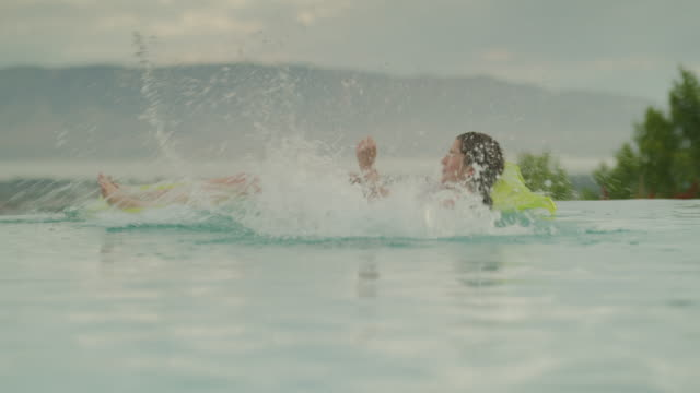 Girl surprising friend floating on pool raft by jumping into swimming pool / Cedar Hills, Utah, United States