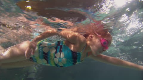 stockvideo's en b-roll-footage met la ms pan girl swimming across pool and wearing swim goggles / riverhead, new york, usa - swimwear