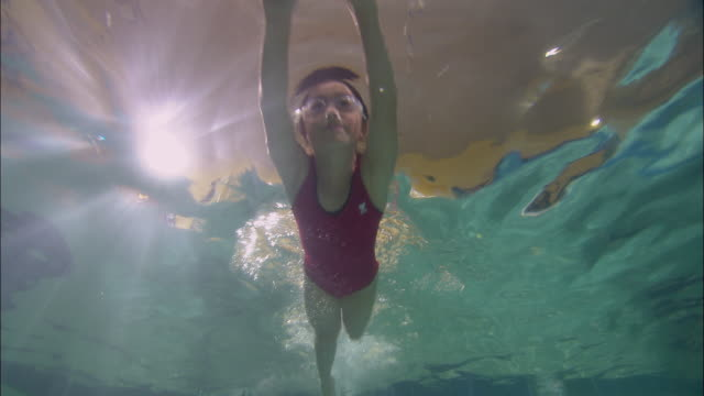 LA WS Girl swimming toward and above camera in pool and wearing swim goggles / Riverhead, New York, USA