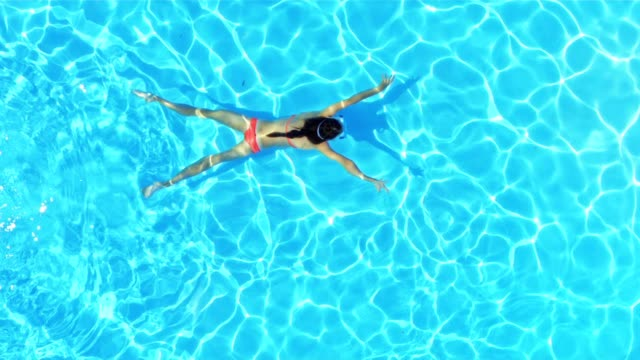SLO MO Girl swimming underwater across a pool