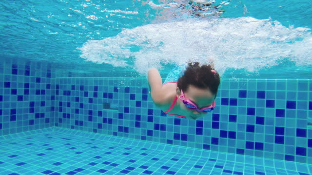 girl swimming underwater and picking up toys from bottom of pool - underwater film camera stock videos & royalty-free footage