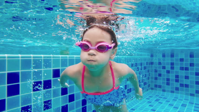 girl swimming underwater and picking up toys from bottom of pool - swimming stock videos & royalty-free footage