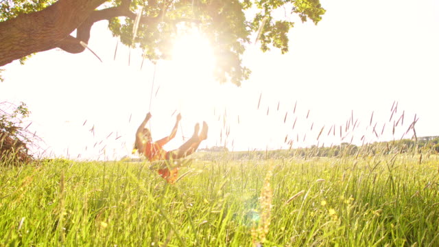 vidéos et rushes de slo missouri fille balançoires et sauter sur le swing - balançoire