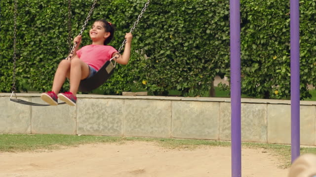 girl swinging at park, faridabad, haryana, india - schwingen stock-videos und b-roll-filmmaterial
