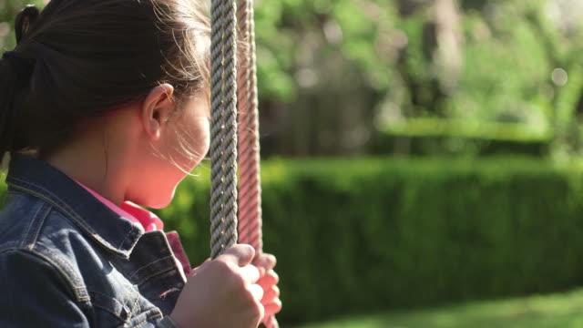 vídeos de stock, filmes e b-roll de girl swinging in park - jaqueta jeans