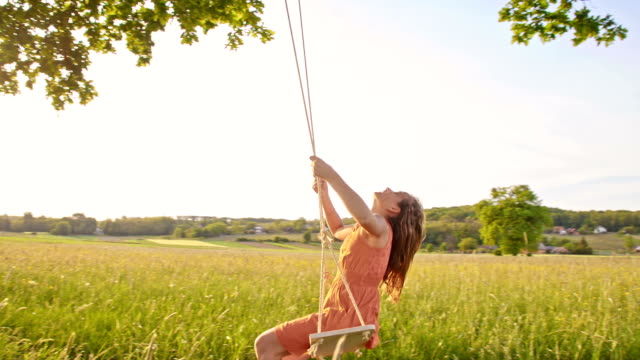 slo mo girl swinging in the meadow - rope swing stock videos & royalty-free footage