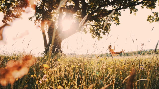 Girl swinging in the middle of the meadow