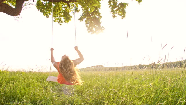 slo mo girl swinging on a tree swing - rope swing stock videos & royalty-free footage