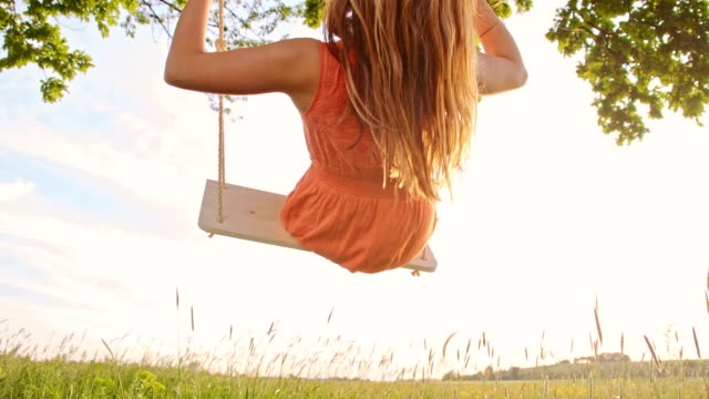 SLO MO Girl swinging on a tree swing