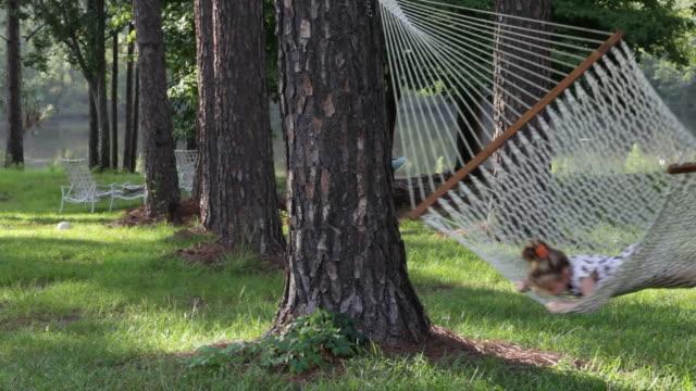 ws pan girl swinging on hammock  / st. simon's island, georgia, usa - nur mädchen stock-videos und b-roll-filmmaterial