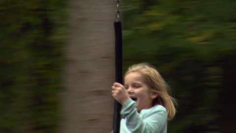 ms swish pan girl (10-11) swinging on rope swing between trees / norwich, norfolk, united kingdom - swish pan stock videos & royalty-free footage