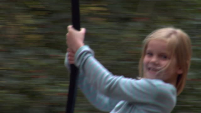 vidéos et rushes de ms ts girl (10-11) swinging on rope swing between trees / norwich, norfolk, united kingdom - panoramique rapide