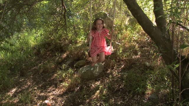 girl swinging on rope swing - ハウテング州点の映像素材/bロール